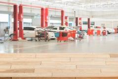 在模糊的汽车的木台式在背景的小服务站 免版税库存图片