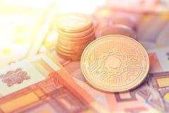 在模糊的背景的发光的金黄科学cryptocurrency硬币与欧洲金钱 库存照片