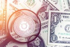 在模糊的背景的发光的金黄科莫多岛cryptocurrency硬币与美元金钱3d例证 库存图片