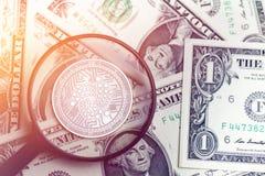 在模糊的背景的发光的金黄IOTA cryptocurrency硬币与美元金钱3d例证 免版税库存照片