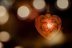 在模糊的背景的红色水晶装饰心脏 免版税库存照片