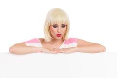 在横幅和看的美好的白肤金发的妇女倾斜下来 库存图片