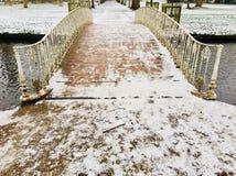 在横渡在一条缓慢流动的河的雪的华丽维多利亚女王时代的金属桥梁小径盖子 库存图片