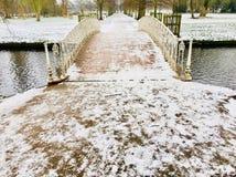 在横渡在一条缓慢流动的河的雪的华丽维多利亚女王时代的金属桥梁小径盖子 图库摄影