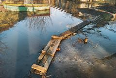 在横跨小河的桥梁折叠的板条板在春天期间充斥高潮反对小船,在镇街道的篱芭 库存图片