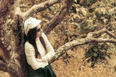 在樱桃树下的寂寞妇女 免版税库存图片