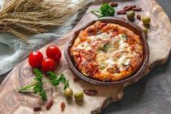 在橄榄一个美丽的自然黑板的圆的香肠烘饼Margherita  选择聚焦 免版税库存照片