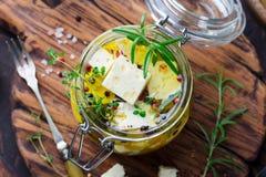 在橄榄油用卤汁泡的希腊白软干酪用在玻璃瓶子的新鲜的草本 木背景 顶视图 图库摄影
