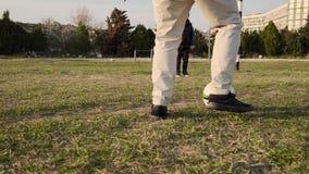 在橄榄球场下的儿子和父亲奔跑和踢在日落慢动作的球 影视素材