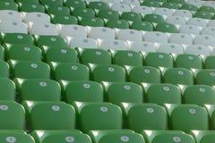 在橄榄球场的塑料绿色和白色位子 图库摄影