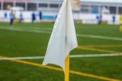 在橄榄球场的背景的白色壁角旗子特写镜头 库存照片