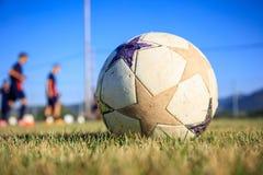 在橄榄球场背景的足球 库存照片