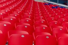 在橄榄球场连续倒空红色塑料椅子 库存图片