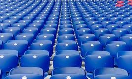 在橄榄球场连续倒空蓝色塑料椅子 库存照片