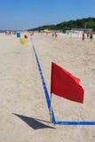 在橄榄球球场的红旗在海滩 库存图片