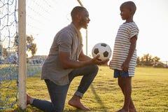 在橄榄球赛期间,父亲给一个球他的儿子 图库摄影