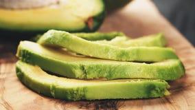 在橄榄色的切板的切的成熟鲕梨 库存照片
