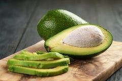 在橄榄色的切板的切的成熟鲕梨 库存图片