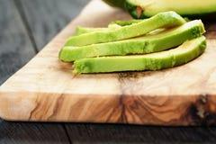 在橄榄色的切板的切的成熟鲕梨 免版税库存图片