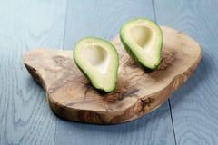 在橄榄色的切板的切的成熟鲕梨 免版税图库摄影