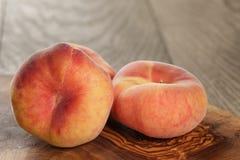 在橄榄色的委员会的成熟平的桃子 库存照片