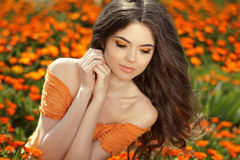 在橙色万寿菊的户外少妇画象开花 免版税库存图片