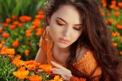 在橙色万寿菊的户外少妇画象开花 免版税库存照片