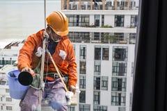 在橙色制服和盔甲的工业登山人风窗清洁器 免版税图库摄影