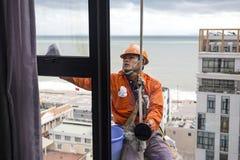 在橙色制服的工业登山人风窗清洁器 免版税库存照片