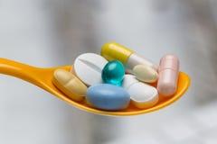 在橙色匙子关闭的五颜六色的药片 免版税库存图片
