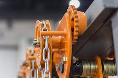 在橙色卷扬机的工业钢链子 库存图片