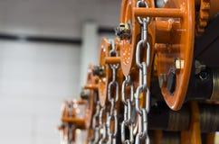 在橙色卷扬机的工业钢链子 免版税库存照片