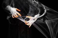在橙色和白色的蠕动的万圣节手与蜘蛛网,蛇神手 免版税图库摄影