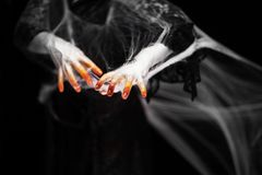 在橙色和白色的蠕动的万圣节手与蜘蛛网,蛇神手 库存照片