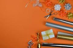 在橙色地面的礼品包装材料器物 免版税库存照片