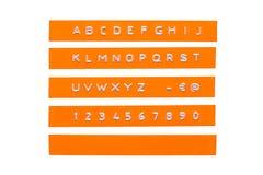 在橙色塑料磁带上的压印的字母表 图库摄影