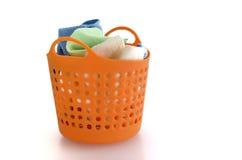 在橙色塑料篮子的织品在白色 免版税库存图片