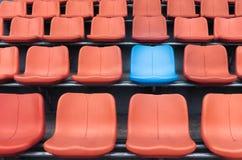 在橙色塑料观看席中行的一把蓝色椅子  库存图片