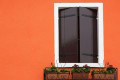 在橙色墙壁上关闭的窗口快门 免版税图库摄影