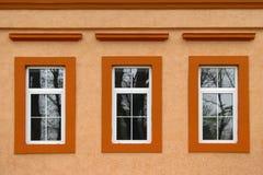 在橙色墙壁上的三个窗口 库存照片