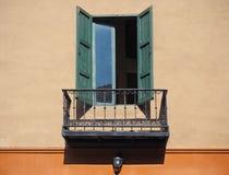 在橙色墙壁上的木窗口有阳台的 图库摄影