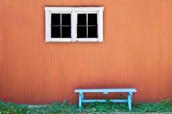 在橙色墙壁上的空的长凳 库存照片