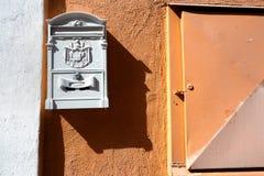 在橙色墙壁上的葡萄酒白合金邮箱,在右边文本的空白的白色空间 库存照片