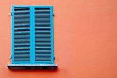 在橙色墙壁上的蓝色窗口 免版税库存图片