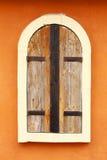 在橙色墙壁上的闭合的木视窗 库存照片
