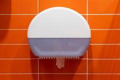 在橙色墙壁特写镜头的白色塑料洗手间分配器 库存照片