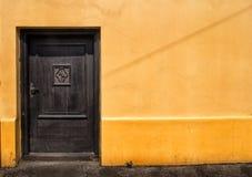 在橙色墙壁的黑暗的门 免版税库存图片