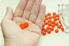 在橙色壳谎言的两种片剂在您的手棕榈  库存图片
