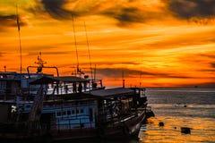 在橙色天空的小船 库存照片
