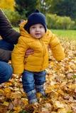 在橙色夹克的孩子保留妈咪 免版税库存图片